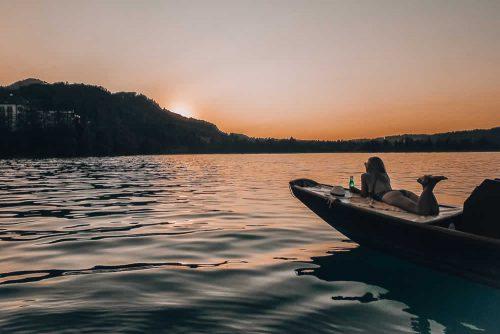 Eine Frau liegt auf einem Boot vor dem Hintergrund des Schloss Fuschl Hotels