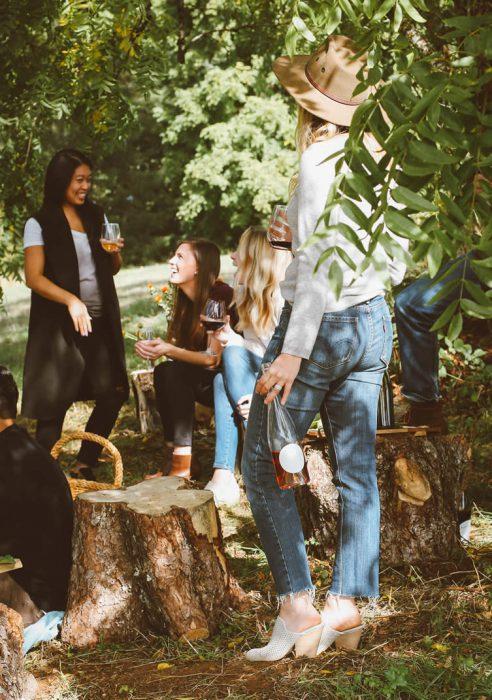 Vier Frauen unter einem Baum trinken Wein.