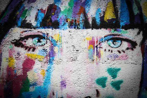 Ein buntes Graffiti, das das Gesicht einer jungen Frau zeigt.