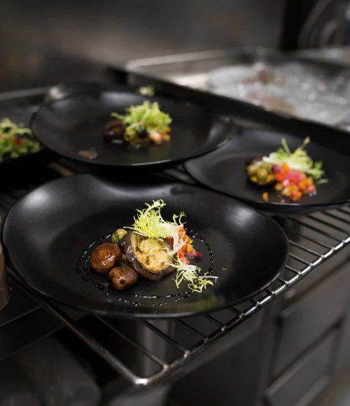 Pilze, Melanzani und Oliven verziert mit ein wenig Salat, arrangiert auf einem schwarzen Teller.