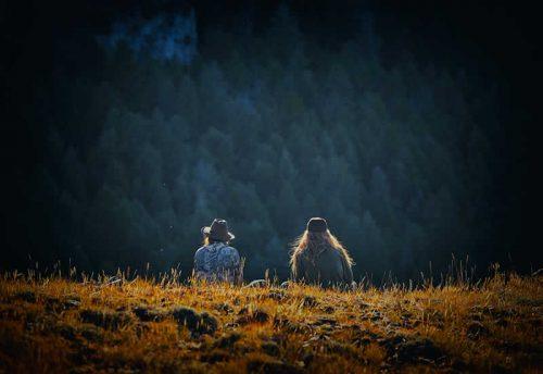 Ein junger Mann sitzt neben einer jungen Frau auf einer Anhöhe im Wald.