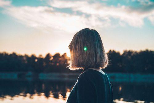 Eine Frau steht mit dem Rücken zu dir an einem einsamen und verlassenen See bei Sonnenuntergang.