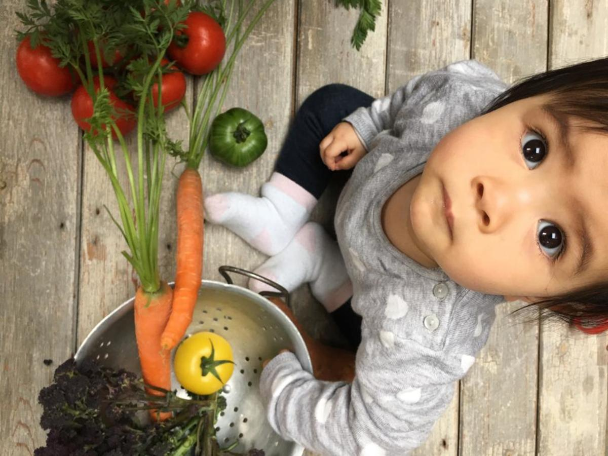 A baby surrounded by vegetables