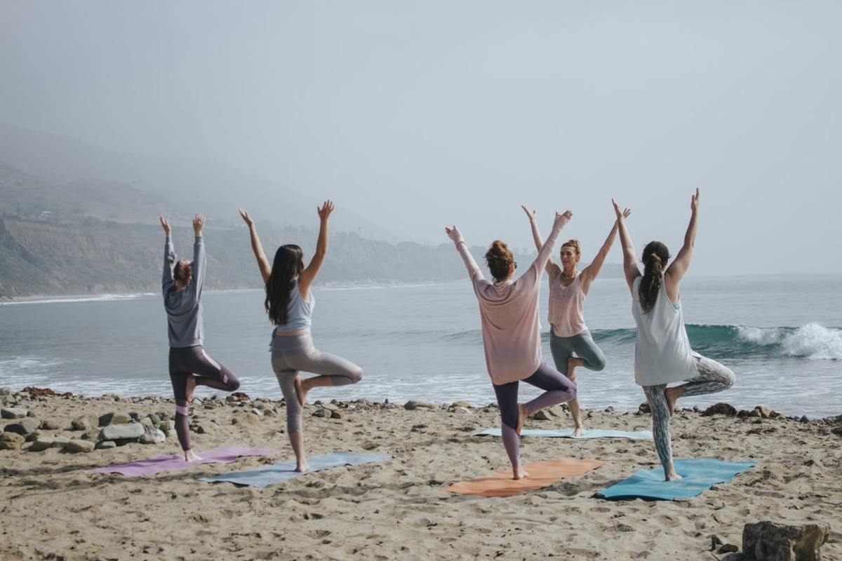 Mothers doing yoga exercises on a beach