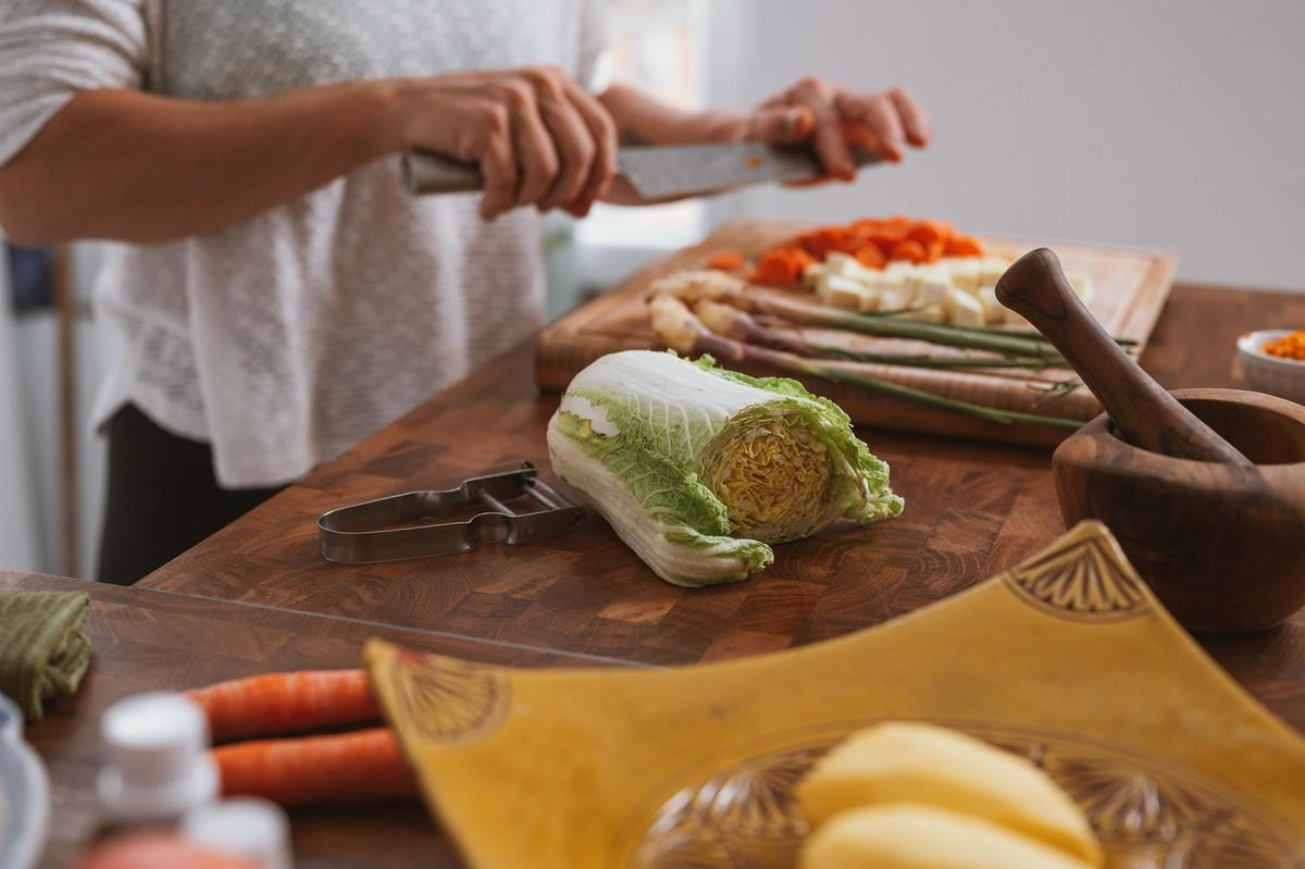 A woman cutting various vegetables on a chopping board