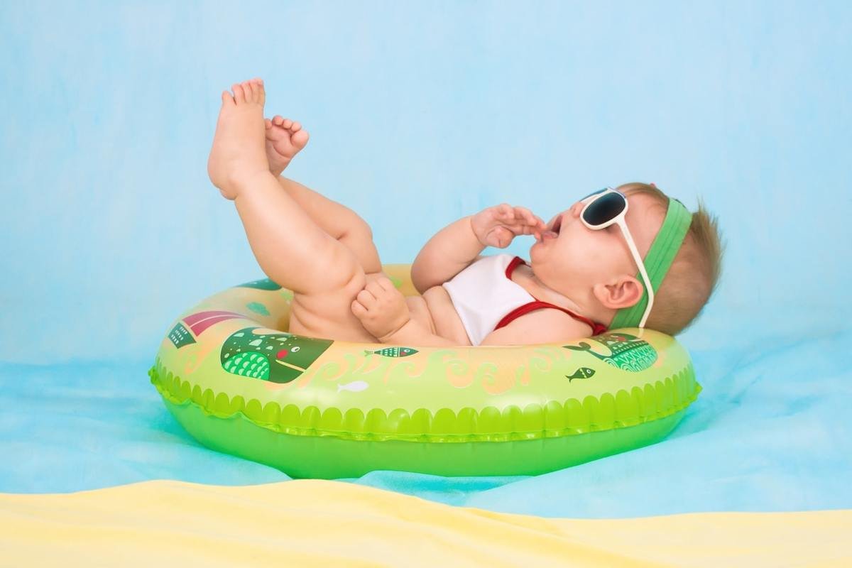 A baby wearing sunglasses and lying on an inflatable ring