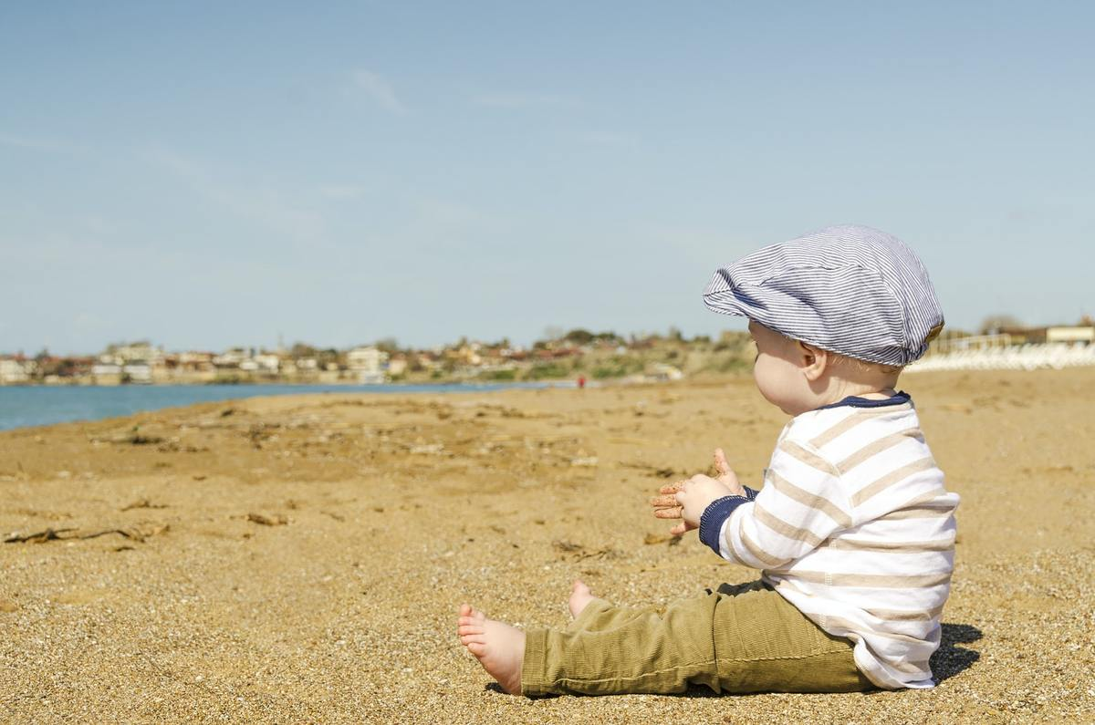 A baby in a hat sat on and sandy beach and looking at the ocean