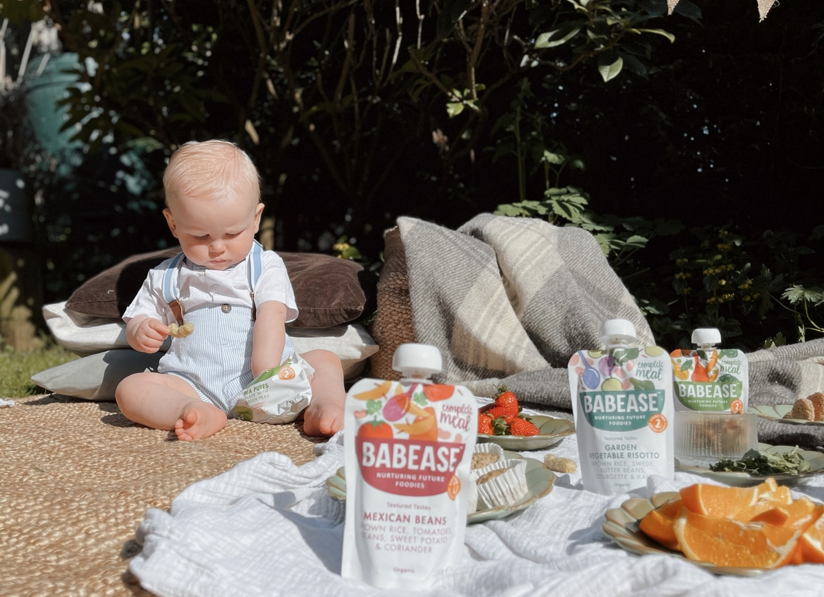 A baby eating from a Babease finger food pack and sat on a picnic blanket