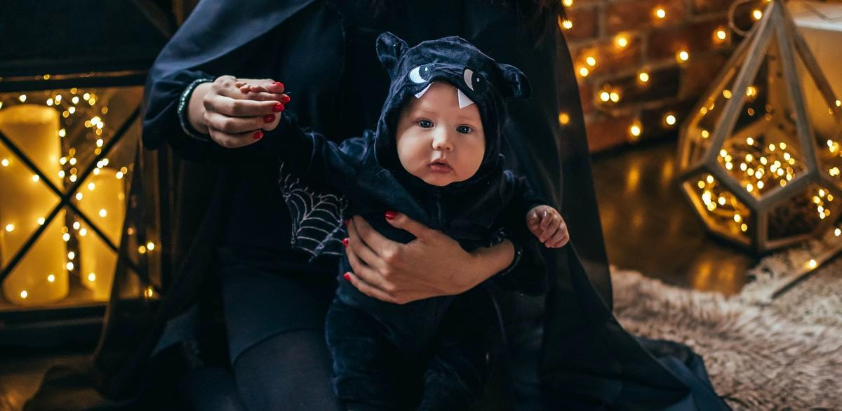 A baby dressed as a bat surrounded by pumpkins