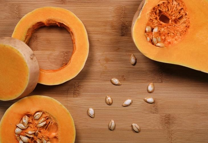 A butternut squash being cut into slices and rings on a cutting board