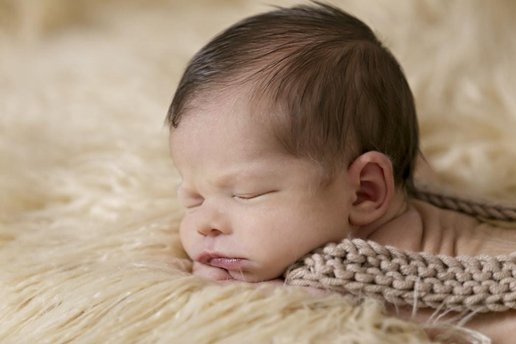 A baby sleeping on a cosy rug
