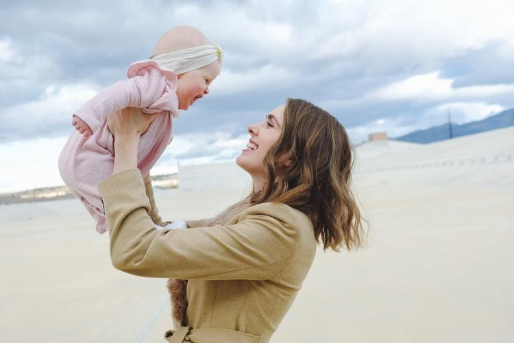 A mother and baby daughter smiling together at a beach