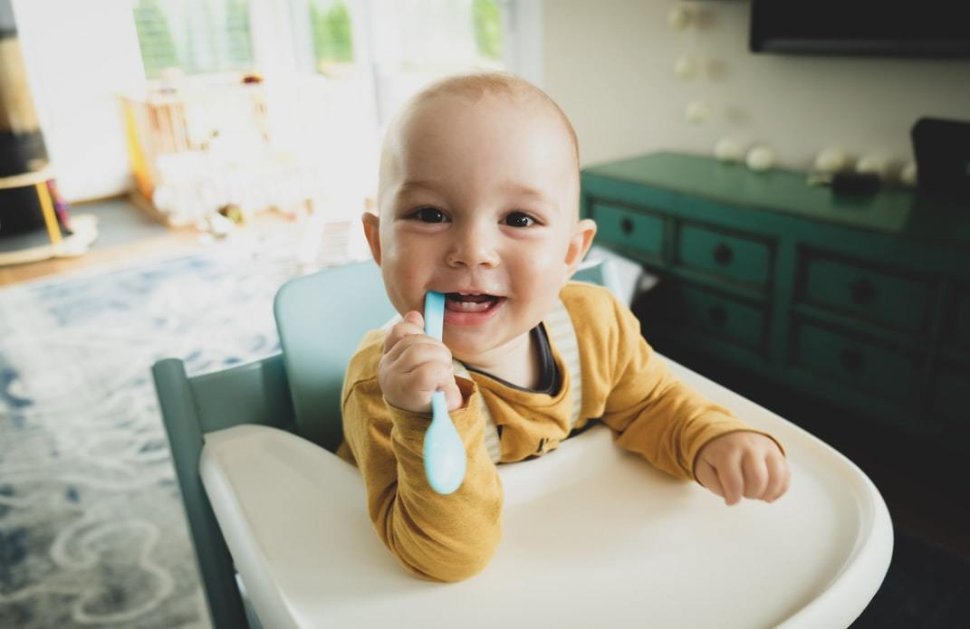 A baby chewing on a weaning spoon