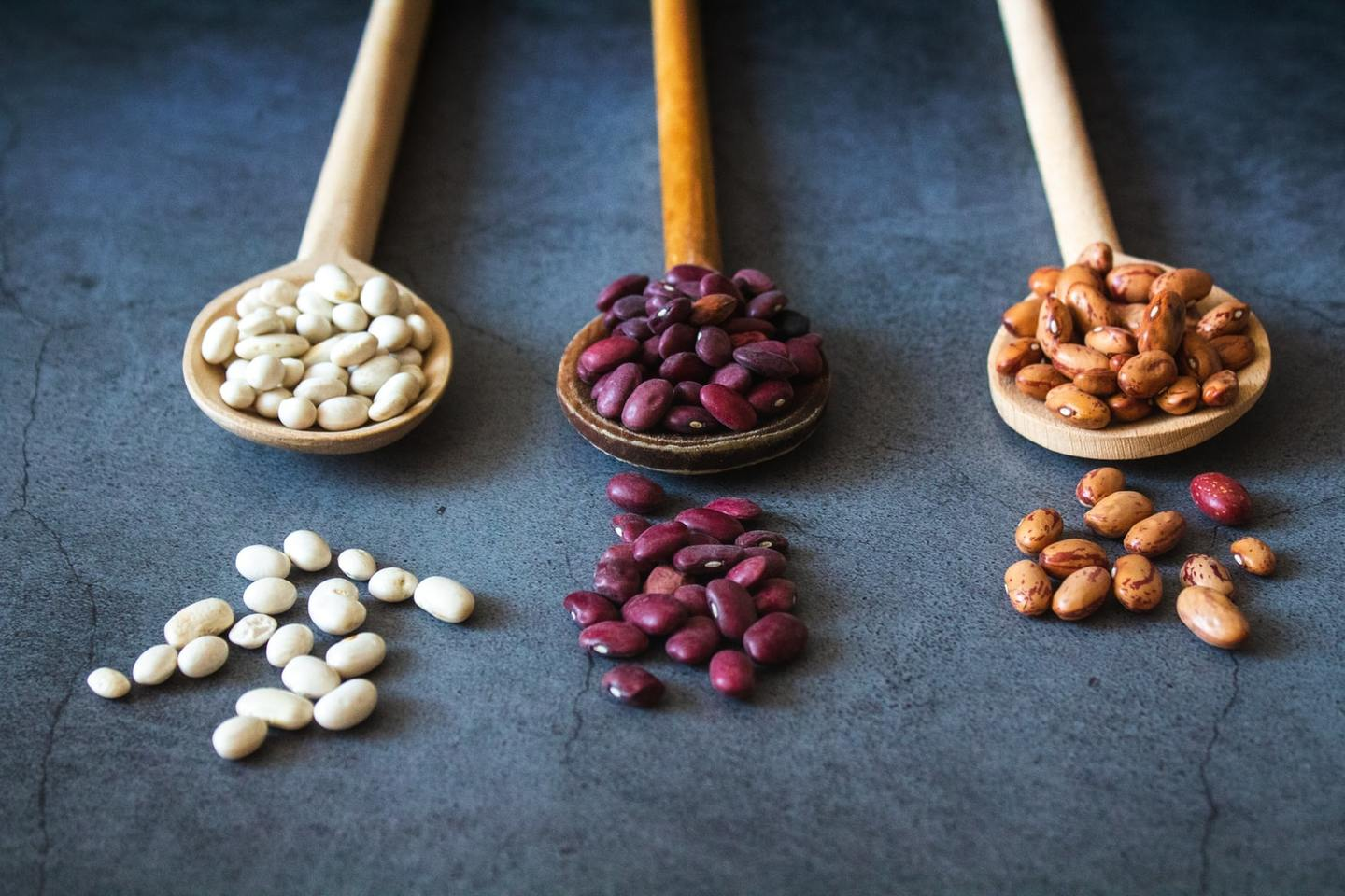 Different kinds of beans on wooden spoons