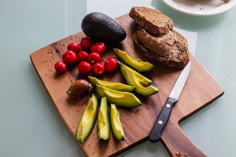 A chopping board with healthy food including avocado and wholegrain bread