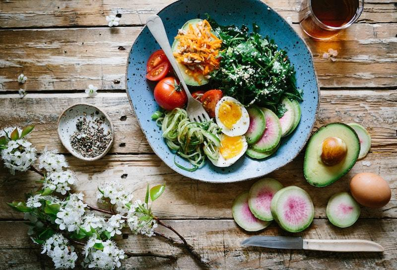 A bowl of healthy food including avocado, egg, spinach and tomato