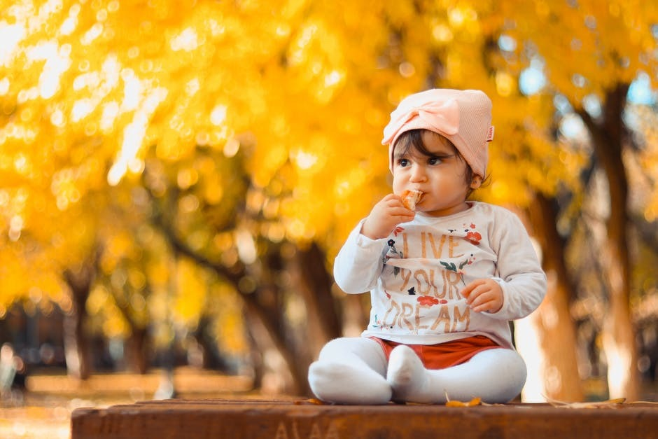 A young child eating outside