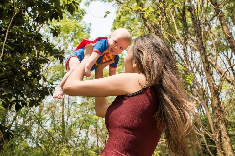 A mother holding her smiling baby in a superman costume
