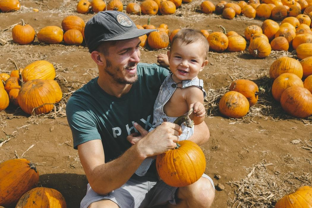 A dad and his baby at a pumpkin field