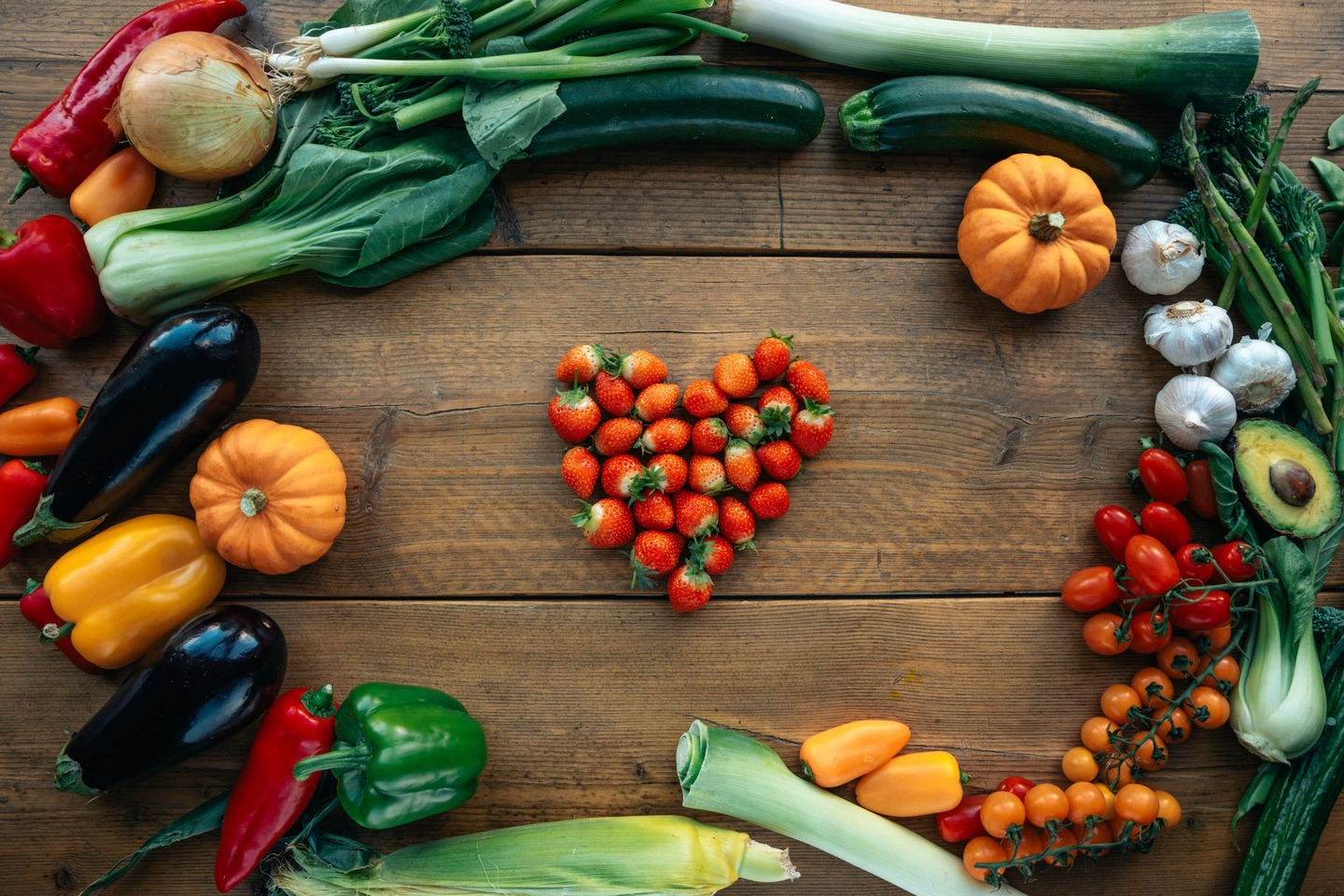 Various vegetables surrounding a heart made out of strawberries
