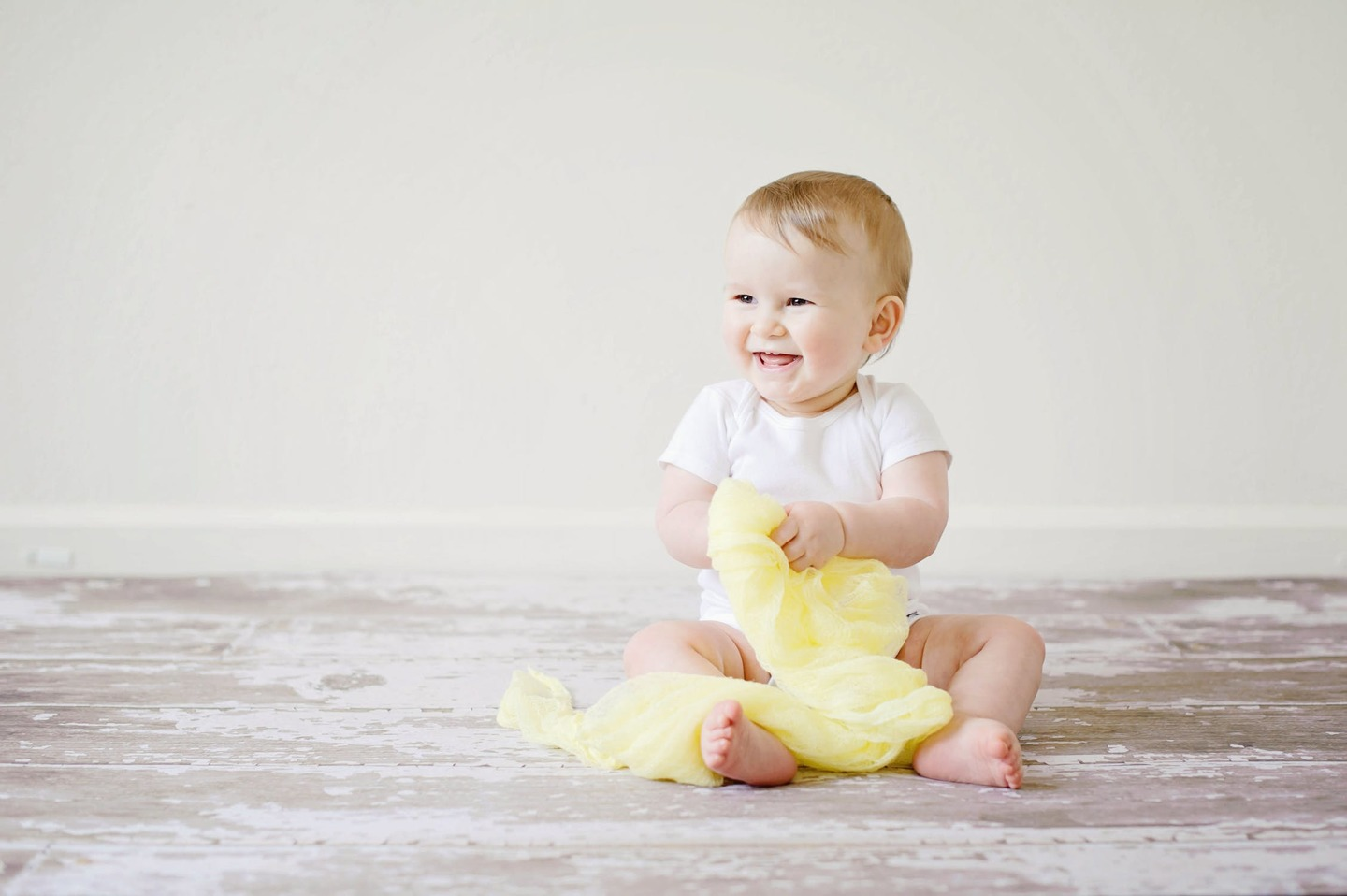 A baby smiling and holding a yellow blanket