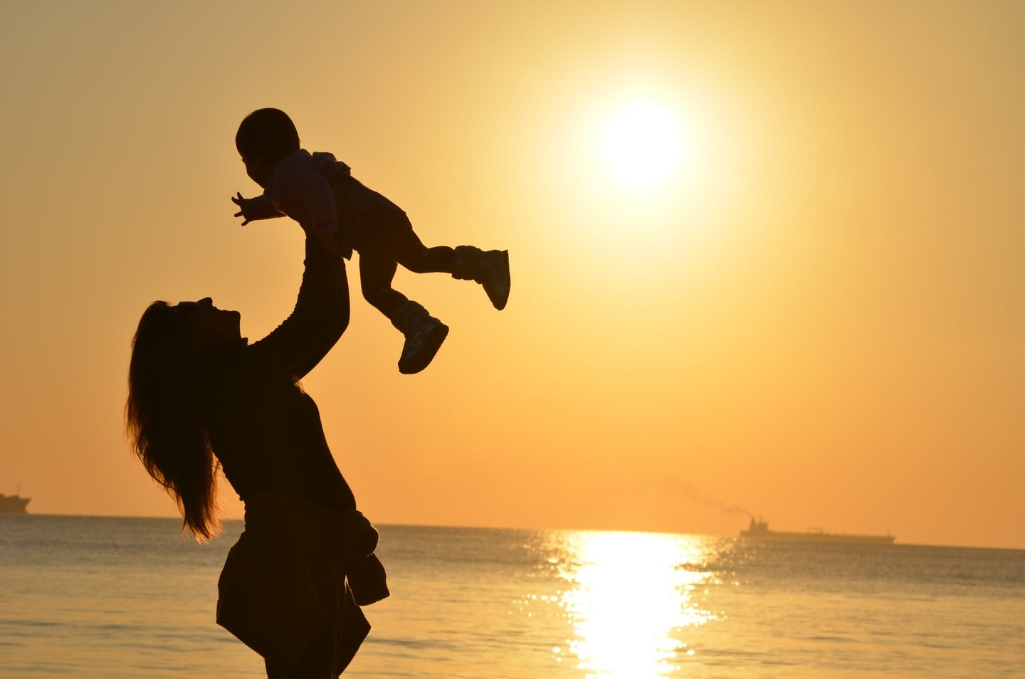 A mother and baby playing at the beach at sunset