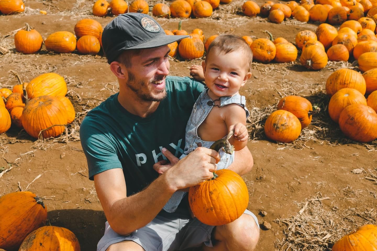 A parent and baby in a pumpkin patch