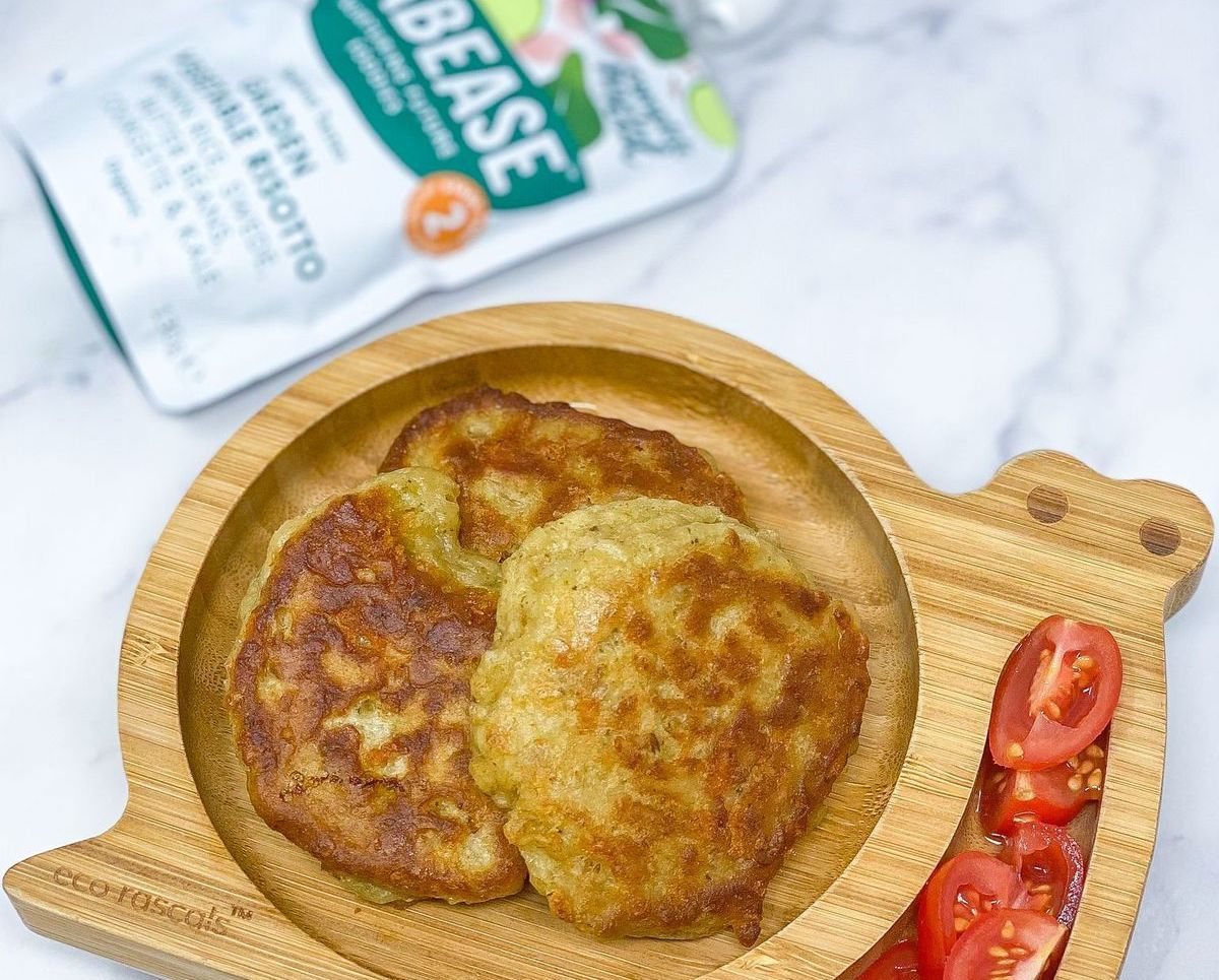 Babease fritters on a wooden baby weaning plate with chopped tomatoes