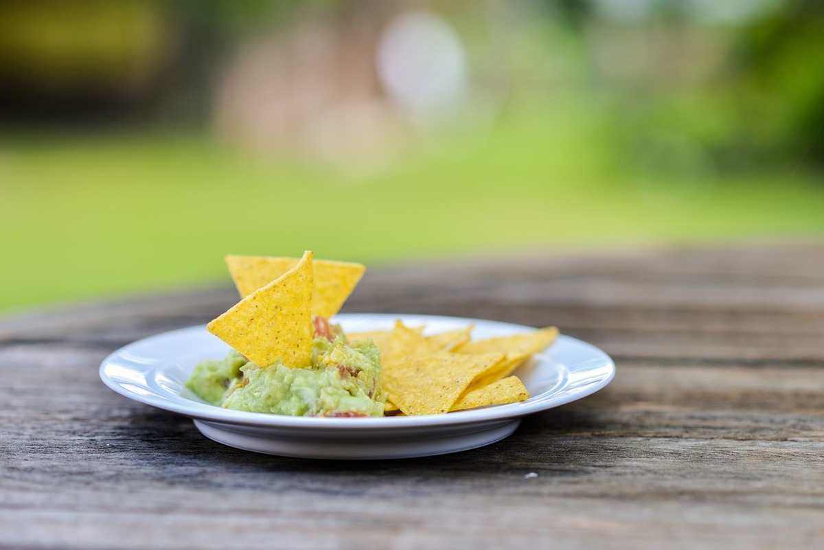 A plate of tortilla chips served with guacamole