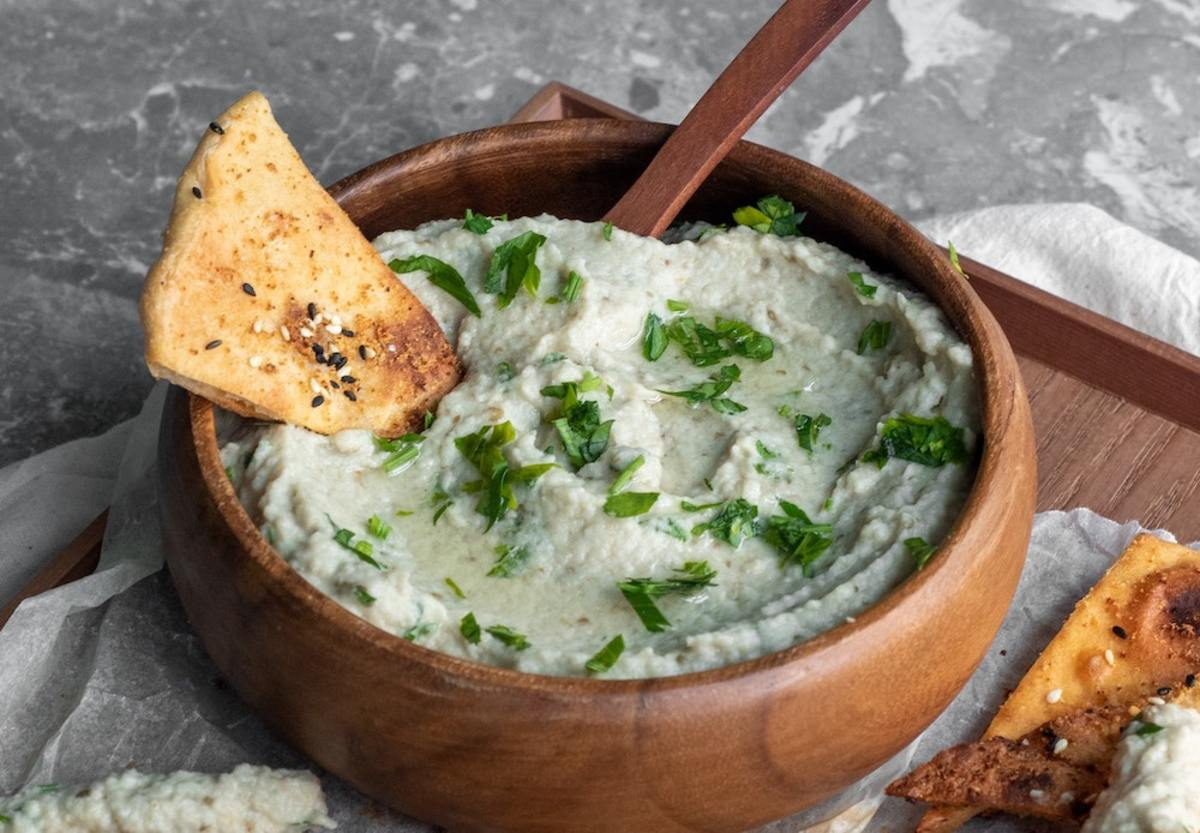 A bowl of baba ganoush with pita chips