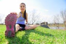 Fiatal nő sport előtt nyújtási gyakorlatot végez