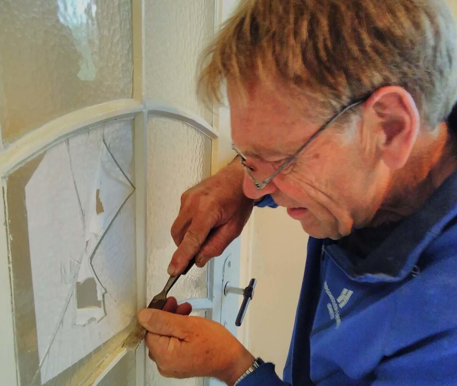 Helge Jensen er en av mange som er med i Vennelaget til Lystgården og bidrar med verdifullt praktisk arbeid. Her er det en av de gamle ærværdige dørene som får nytt vindu på forskriftsmessig vis.
