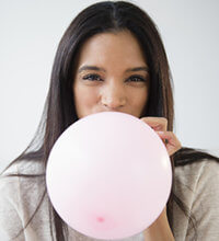 woman blowing up balloon