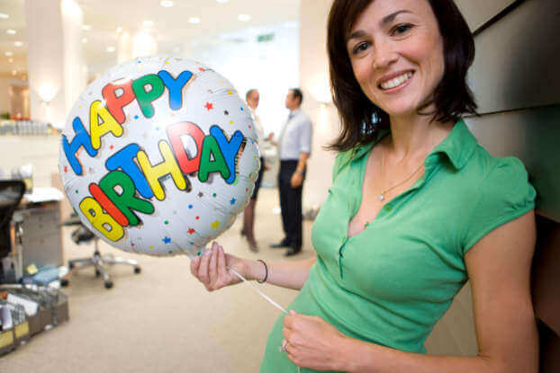 a woman holding a happy birthday balloon gift