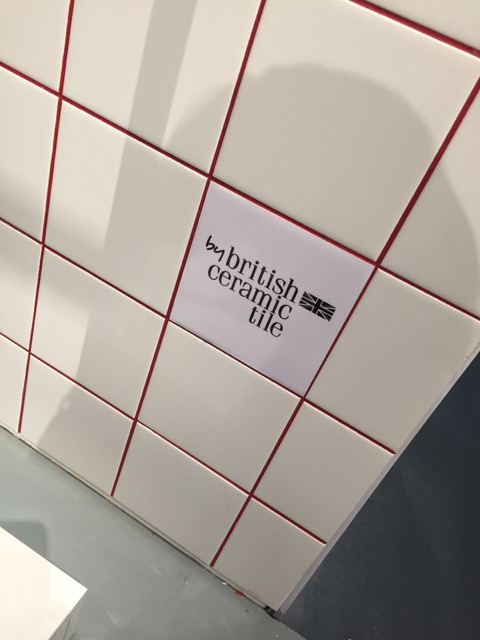 close up of ivory tiles with red grouting and british ceramic tile logo