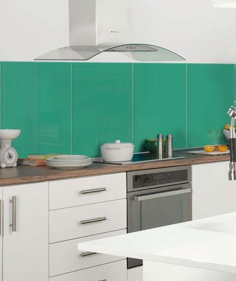 glass splashback in green shown with multiple splashbacks with white kitchen and wood worktops