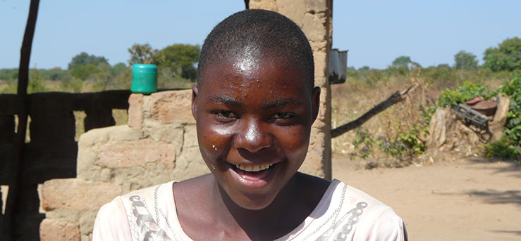 Sponsor a child in Zambia like Brenda - image shows brenda outside her house