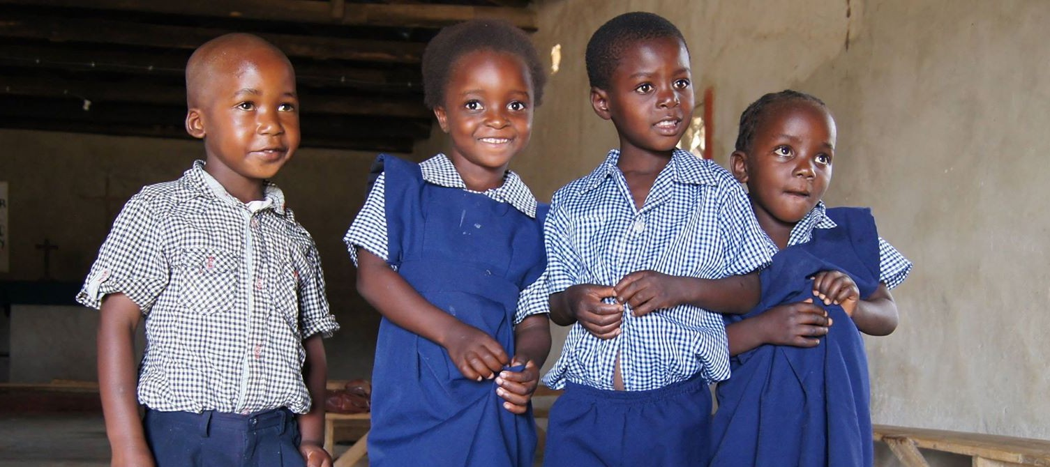 Image of four sponsored children in school in Zambia