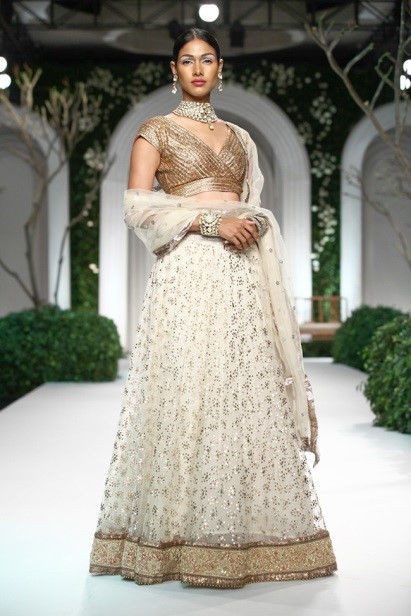 A rich white and gold bridal lehenga by Meera and Muzaffar Ali