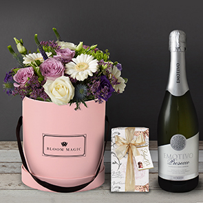 S'aimer Sur Le Pont Neuf Gift Set Flowers Delivered - S'aimer sur le Pont Neuf is a beautiful arrangement of hatbox flowers features a mixture of purple and white roses, lisianthus, and gerbera. This hatbox is expertly arranged by hand and presented in your choice of a blush pink, powder blue or charcoal grey hatbox. The S'aimer sur le Pont Neuf is perfect for any occasion and we guarantee it will put a big smile on her face!