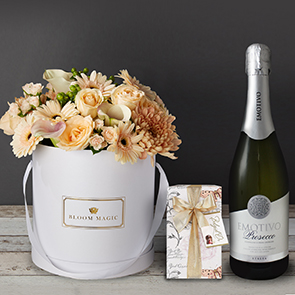 Bonheur à Versailles Gift Set Flowers Delivered - This bouquet is a pastel paradise. It features white calla lilies and white roses, expertly arranged by hand and presented in your choice of a pearl white or matte black hatbox  No two bouquet are ever the same so each and every bouquet is bespoke and truly unique. The picture shows an example of our bouquet with yours containing seasonal flowers similar in colour, texture and vibrancy.  Note: On delivery, you may notice some tougher, slightly browned petals around the outside of your roses or other flowers. Rest assured, the flowers are fresh!These are called 'storm petals' which we intentionally leave on to protect the delicate inner flower when in transit. To reveal the fresh inner petals, gently remove the 3/4 storm petals by pulling them at the base