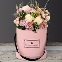 Jardins du Luxembourg is a beautiful arrangement of hatbox flowers featuring spray roses and vintage carnations.