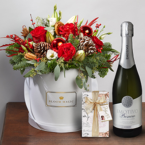 Le Père Noël Gift Set Flowers Delivered - Our signature holiday hatbox arrangement is sure to bring festive cheer to any home. Filled with gorgeous seasonal blooms in warm tones set artfully in our gorgeous pearl white XL hatbox. Le père Noël is part of the Bloom Magic Christmas Collection.