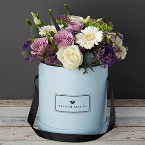 Rêverie à Saint-germain Flowers Delivered - This beautiful flower arrangement features a mixture of purple and white roses, lisianthus, and gerbera. It is expertly arranged by hand and presented in your choice of a powder blue or charcoal grey hatbox.