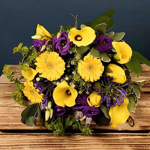 Sunny South East Flowers Delivered - Inspired by the hues of a summer meadow along the Wild Atlantic Way, this exception and popular bouquet features muted lilacs and deep purple are set off by vivid yellow callas.