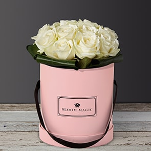 Une Nuit À Montmartre is an elegant bouquet of pure white avalanche roses. This arrangement of flowers is perfect for a romantic occasion or a birthday. This can be sent as a sympathy bouquet of flowers as well, and would look more subdued in a charcoal gray hatbox.