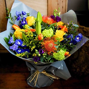 Zeus Flowers Delivered - A striking mix of bright yellow, burned orange and deep blue flower shades make 'Zeus' our most vibrant bouquet. It is perfect for that happy occasion or to put a big smile back on someone's face.