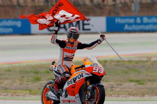 Marc Márquez celebrates on his RC213V holding flag