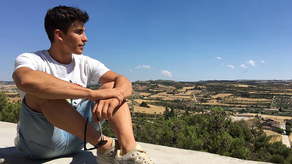 Marc Márquez sentado sobre murete en día soleado