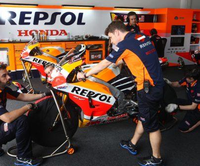técnicos en el box del equipo repsol realizando el mantenimiento de una MotoGP